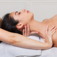 Female beautician doctor with patient in spa wellness center. Professional cosmetologist make body shoulders and neck relaxing massage to beautiful indian girl in cosmetology cabinet or beauty parlor.