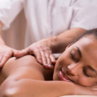 Relaxed young happy pretty woman and massage for painful shoulder